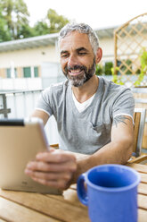 Portrait of smiling man sitting on his balcony using digital tablet - MBEF001121