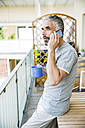 Man on his balcony telephoning with smartphone  holding cup of coffee - MBEF001230