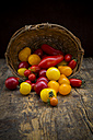 Basket of different organic heirloom tomatoes on wooden table - LVF001869