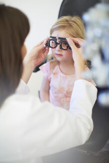 Eye doctor examining girl's vision - ZEF000604