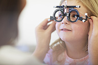 Eye doctor examining girl's vision - ZEF000605