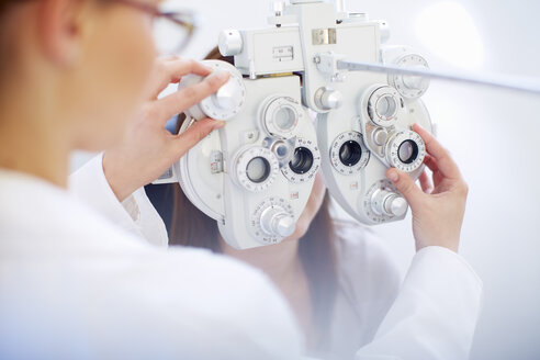 Eye doctor examining woman's vision - ZEF000608