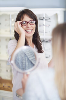Woman at the optician trying on glasses - ZEF000644