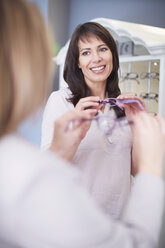 Woman at the optician trying on glasses - ZEF000620