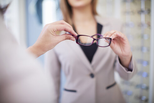 Woman at the optician trying on glasses - ZEF000657