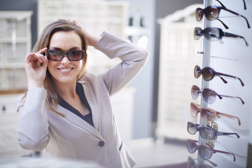 Woman at the optician trying on sunglasses - ZEF000698