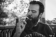 Man with full beard smoking cigarette on porch - KOF000024