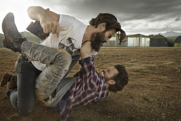 Two men with full beards fighting in abandoned landscape - KOF000030