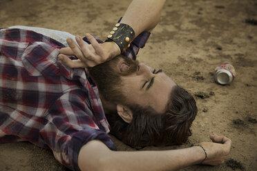 Man with full beard lying on soil - KOF000037