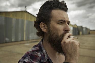 Man with full beard smoking cigarette - KOF000039