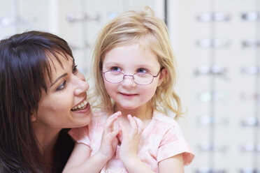 Girl at the optician trying on glasses - ZEF000596