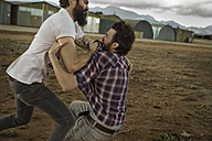 Two men with full beards fighting in abandoned landscape - KOF000042
