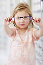 Girl at the optician holding glasses - ZEF000597