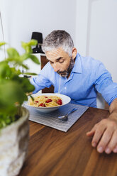 Man eating pasta in his kitchen - MBEF001138