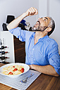 Man eating pasta in his kitchen - MBEF001158