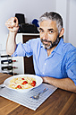Portrait of man eating pasta in his kitchen - MBEF001139