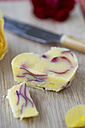Rose butter and rose petals on chopping board - MYF000551