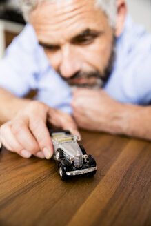 Man playing with toy cars - MBE001143