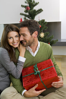 Happy couple with Christmas present at home - CHAF000189