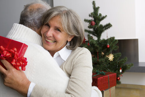Senior couple exchanging Christmas presents at home - CHAF000192