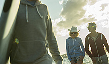 Three teenagers walking on the beach at evening twilight - UUF001702