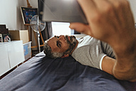 Serious looking man lying on his bed taking a selfie with his smartphone - MBEF001217