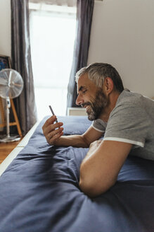 Smiling man lying on his bed looking at his smartphone - MBEF001160