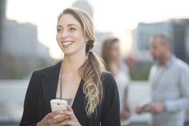 Portrait of smiling businesswoman with smartphone - ZEF000259