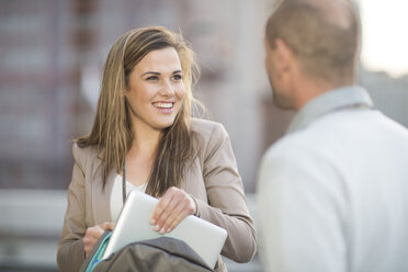 Portrait of smiling businesswoman communicating with a colleague - ZEF000261