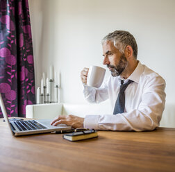 Portrait of businessman working at home office drinking coffee - MBEF001232