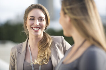 Portrait of smiling businesswoman communicating with another one - ZEF000263