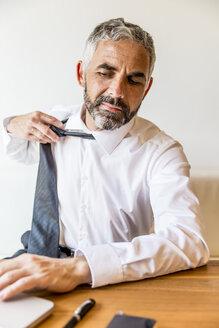 Businessman loosening his tie - MBEF001154
