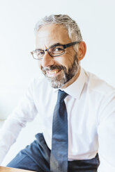 Portrait of smiling businessman wearing glasses - MBEF001156