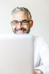 Portrait of laughing businessman working at laptop - MBEF001165