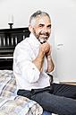 Portrait of smiling businessman binding tie in his bedroom - MBEF001169