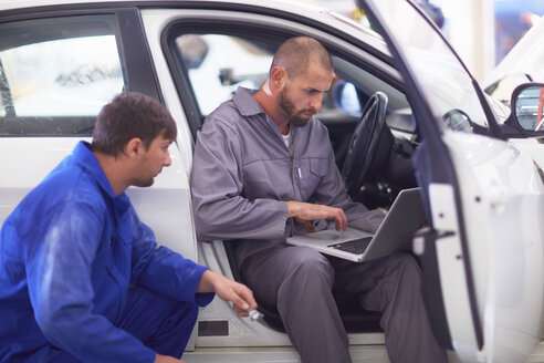 Two car mechanics with laptop in repair garage - ZEF000511