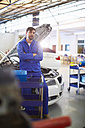 Confident car mechanic in repair garage - ZEF000517