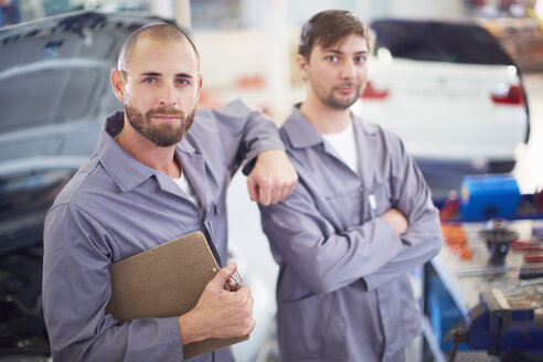 Two car mechanics with clipboards in repair garage - ZEF000522
