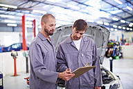 Two car mechanics with clipboards in repair garage - ZEF000523