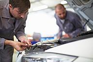 Two car mechanics at work in repair garage - ZEF000545