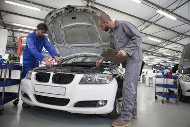 Two car mechanics at work in repair garage - ZEF000573