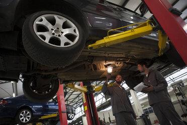Two car mechanics at work in repair garage - ZEF000738