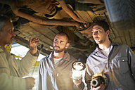 Two car mechanics with client in repair garage - ZEF000507