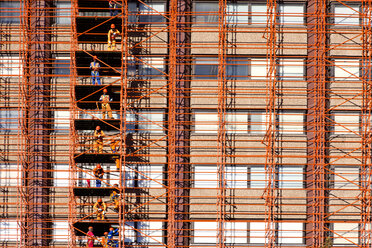 South Africa, Cape Town, row of construction workers standing on scaffolding of high-rise building - ZE000852
