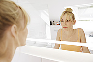 Woman looking at her mirror image in the bathroom - GDF000421