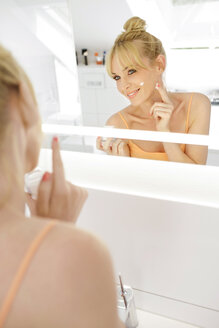 Smiling woman looking at her mirror image while applying face cream - GDF000424