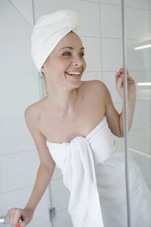 Portrait of smiling woman wearing towels  in the bathroom - GDF000428