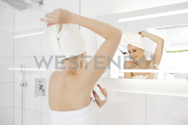 Woman looking at her mirror image while applying deodorant in the bathroom - GDF000429 - Gabi Dilly/Westend61