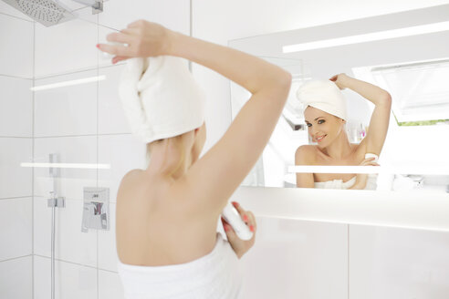 Woman looking at her mirror image while applying deodorant in the bathroom - GDF000429