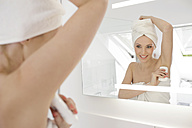 Mirror image of woman applying deodorant in the bathroom - GDF000430